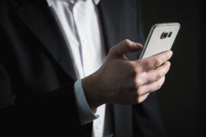 Mann im Anzug hält ein Handy. Ob er vom Support-Ende von Windows 10 Mobile betroffen ist?