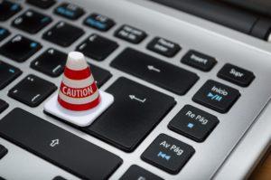 """Zu sehen ist ein Laptop, auf dessen Tastatur ein kleines Warnhütchen mit dem Wort """"Caution"""" (Deutsch: Vorsicht) steht. Bild: www.pixabay.de/ferarcosn"""