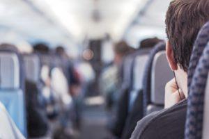 Zu sehen ist das Innere eines Flugzeugs. Links und rechts des Mittelgangs sind die Sitze mit Passagieren besetzt. Man sieht sie von hinten. Dank WLAN im Flugzeug können sie unterwegs arbeiten. Bild: www.pixabay.com/RyanMcGuire