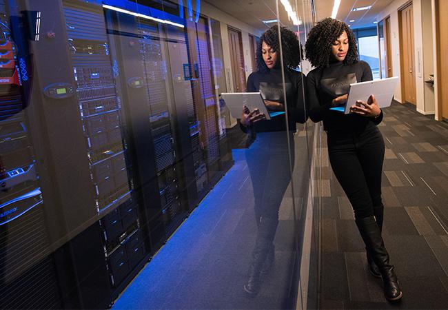 Eine Frau steht in einem Serverraum. Die optimale Serverraumtemperatur ist hier reguliert. Bild: Unsplash/Christina Morillo