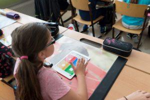 Zu sehen ist ein Mädchen, das mit einem Tablet in der Hand an seinem Pult im Klassenzimmer sitzt. Mit dem DigitalPakt Schule soll dieses Bild zum Alltag gehören. Bild: www.pixabay.com / Steve Riot
