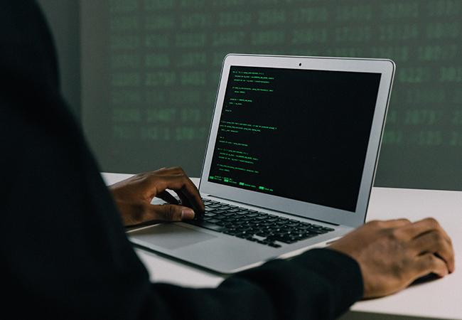 Ein Laptop steht auf einem Schreibtisch und jemand tippt auf der Tastatur. Hacker-Angriffe sind besonders gefährlich. Bild: Pexels/Mati Mango