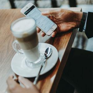 Zu sehen ist ein Tisch, auf dem ein Kaffee abgestellt ist, ein Geschäftmann sitzt davor und hält ein Handy in der Hand. Über mobile Anwendungen prüft er seine E-Mails. Bild: www.unsplash.com / Anete Lūsiņa