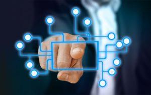 Zu sehen ist ein Geschäftsmann, dessen Hand auf ein versinnbildlichtes Netzwerk verschiedener Geräte im Internet der Dinge zeigt. Der Security-by-Design-Ansatz wird hier besonders wichtig. Bild: www.pixabay.com / Gerd Altmann