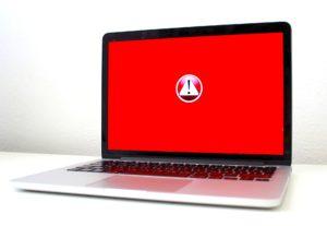 Zu sehen ist ein Laptop auf einem weißen Tisch vor weißem Hintergrund. Der Bildschirm ist rot und enthält einen Warnhinweis. Vielleicht ist der Laptop von der Ransomware GermanWiper befallen. Bild: www.pixabay.com / Michael Geiger