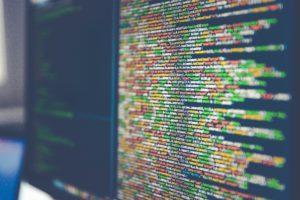 Zu sehen ist ein Monitor mit dem Code einer Software. Ob hier auf Security by Design geachtet wird? Bild: www.unsplash.com / Markus Spiske