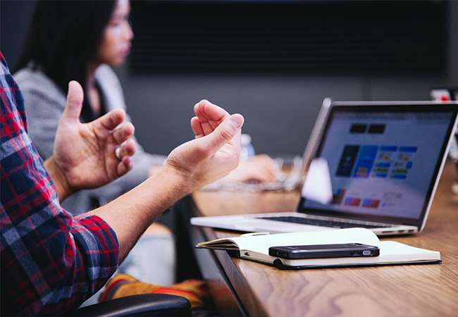 Mitarbeitende diskutieren in einem Meeting. Bild: Unsplah/Headway