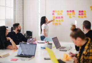 Zu sehen ist ein Meeting, bei dem mehrere Personen an einem Konferenztisch sitzen, während eine Person etwas vorträgt. Vielleicht geht es um Security Awareness. Bild: Unsplash / You X Ventures