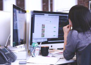 Das Bild zeigt eine Person vor ihrem Computer an einem Büro-Schreibtisch. Cyberkriminalität greift solche Arbeitsplätze an.
