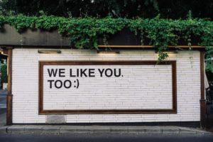 """Das Bild zeigt eine Wand auf der der Spruch """"Wie Like You. Too."""" steht. Sie symbolisiert das Problem mit Paid Likes und dass eine """"Gefällt Mir""""-Angabe längst nicht mehr aussagekräftig ist. Bild: Unsplash/Adam Jang"""