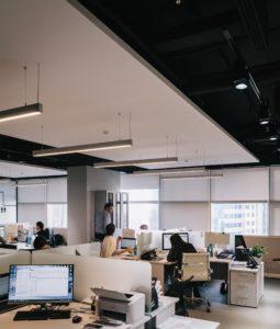 Großraumbüro mit verschiedenen Schreibtischen, leuchtenden Computerbildschirmen und Mitarbeitern.