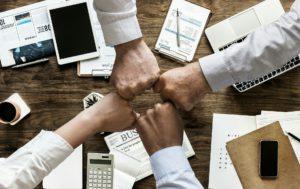 Cyberkriminalität lässt sich durch Zusammenarbeit erfolgreicher abwehren. Dieses Bild zeigt vier Fäuste, die sich ein einem Kreis berühren.