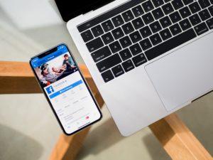 Das Bild zeigt einen Computer und ein Smartphone, auf dem eine Facebook-Seite angezeigt wird. Es symbolisiert, dass Paid Likes auf Facebook sind eine gängige Praxis, um sich Beliebtheit zu erkaufen. Bild: Unsplash/Tim Bennett