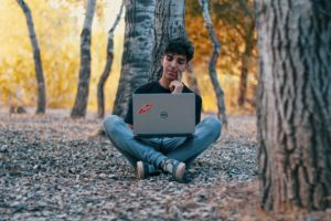 Das Bild zeigt einen jungen Mann, der mit einem Laptop auf dem Schoß im Wald sitzt. Verkörpert er nachhaltige Elektronik? Bild: Unsplash/Hamza Tighza