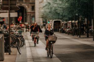 Das Bild zeigt Menschen auf dem Fahrrad in einer Stadt, die das Dienstradleasing symbolisieren sollen. Das fördert auch die Energieeffizienz. Bild: Unsplash/Vitor Pinto