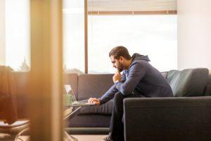 Zu sehen ist ein Mann, der auf dem Sofa sitzt und am Laptop arbeitet. Vielleicht nutzt er Microsoft Teams kostenlos. Bild: Unsplash/LinkedIn Sales Navigator