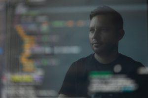 Zu sehen ist die Spiegelung eines Mannes auf einem Bildschirm. Er bietet IT-Services trotz Corona. Bild: Unsplash/Peter G