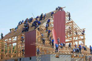 Das Bild zeigt viele Bauarbeiter, die gemeinsam an einem Haus bauen. Betriebsklima verbessern funktioniert auch hier mit entsprechen Mitarbeiter-Plattformen. Bild: Unsplash/Randy Fath