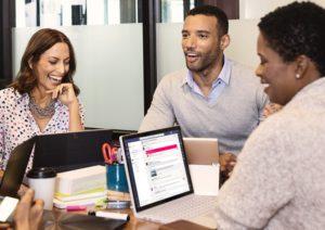 Zu sehen sind drei Kollegen, die mit Microsoft Teams arbeiten. Damit sie zufrieden sind, muss die Microsoft-Teams-Einführung optimiert sein. Bild: Microsoft