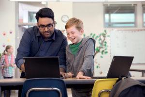 Ein Lehrer zeigt einem Schüler etwas an einem Lenovo-Laptop. Er möchte auch weiterhin die Schule digitalisieren. Bild: Lenovo