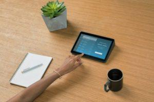 Eine Hand bedient einen Touch-Controller, über den sich Videokonferenz-Systeme einfach steuern lassen. Bild: Logitech