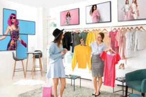 Zu sehen sind Verkäuferin und Kundin in einem Bekleidungsgeschäft, Digital Signage von iiyama wird zur Werbung genutzt. Bild: iiyama