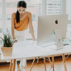 Eine Frau steht selbstbewusst an ihrem Arbeitsplatz und ist in eine Aufgabe vertieft. Sie ist das Sinnbild für Employee Empowerment. Bild: Unsplash/Keren Levand