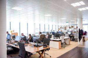 Zu sehen ist eine Bürofläche mit Mitarbeitern an ihren PC-Arbeitsplätzen. Unternehmen können Arbeitsplätze managen lassen. Bild: Unsplash/Arlington Research