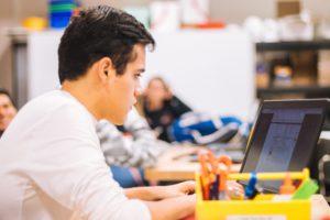 Ein Schüler sitzt mit einem Laptop im Klassenzimmer. Das Gerät wird über die Intel vPro Plattform verwaltet. Bild: Unsplash/Jeswin Thomas