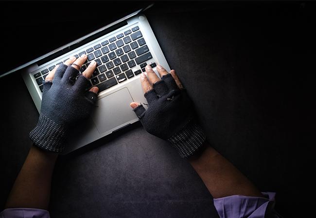 Zu sehen sind behandschuhte Hände, die auf einem Laptop tippen. Es geht um die Cyberangriffe 2020. Bild: Unsplash/Towfiqu barbhuiya