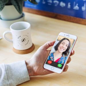 Am Schreibtisch hält eine Hand ein Smartphone, auf dem die smarte Türklingel ein Video einspielt. Bild: Unsplash/Mia Baker; Pexels/Kampus Production