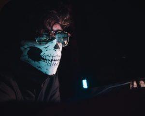 Ein Mann mit Maske sitzt vor einem Bildschirm. Ob er an Cyberangriffe 2020 beteiligt war? Bild: Unsplash/Nahel Abdul Hadi
