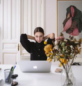 Eine Frau sitzt vor einem Laptop und greift sich in den Nacken. Ist sie verspannt, weil ihr Chef Mitarbeiter überwachen im Home Office gut findet? Bild: Pexels / Polina Zimmerman