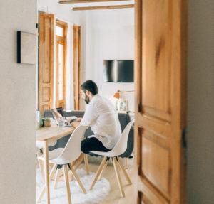 Durch eine Tür sieht man einen Mann mit seinem Laptop am Esstisch arbeiten. Mitarbeiter überwachen im Home Office ist aktuell ein Thema. Bild: Pexels / Nataliya Vaitkevich