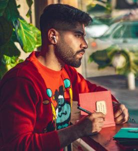 Ein junger Mann nutzt über iPhone und Airpods die Clubhouse-App und macht sich Notizen. Bild: Unsplash / amir riazipour
