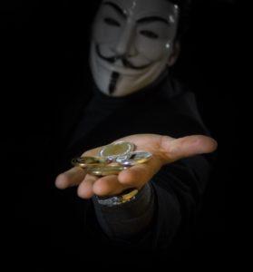 Zu sehen ist eine maskierte Person, die eine Hand mit Bitcoin-Münzen in die Kamera hält. Die Hintermänner der Clop-Ransomware fordern Lösegeld in Bitcoin. Bild: Pixabay / WorldSpectrum