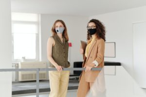 Zu sehen sind zwei Kolleginnen mit Mund-Nase-Schutz im Büro. Mit #MachtsBuerosZu fordern Arbeitnehmer das Recht auf Home Office im Lockdown ein. Foto: Pexels / Edmond Dantès