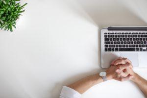 Aus der Vogelperspektive sitzt ein Mann wartend vor seinem Laptop. Ein Update wird ausgespielt, um den Stand der Technik einzuhalten. Bild: Unsplash/NordWood Themes