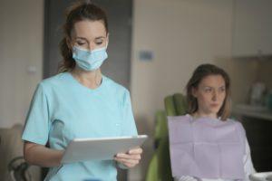 Eine Zahnärztin schaut auf ein Tablet, auf dem sie die elektronische Patientenakte einsehen kann. Eine Patientin sitzt auf dem Behandlungsstuhl. Bild: Pexels/Andrea Piacquadio