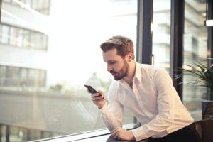Ein Geschäftsmann sieht auf sein Smartphone. Er nutzt darauf Threema Work. Bild: Pexels / Andrea Piacquadio