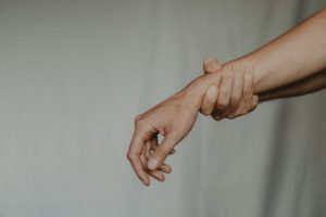 Zu sehen sind zwei Arme, eine Hand umfasst den anderen Unterarm. Schmerzen sind ein Zeichen für das RSI-Syndrom. Bild: Pexels / Anete Lusina