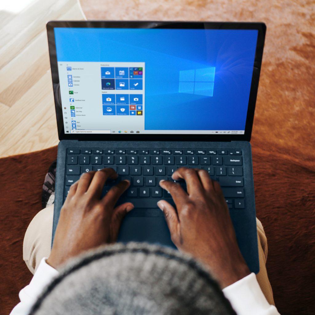 Aus der Vogelperspektive ist ein Mann mit Mütze und einem Laptop auf den Knien zu sehen. Er will keine der veralteten Windows-10-Versionen nutzen und upgraden. Bild: Unsplash/Windows
