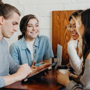 Vier Kollegen, drei Frauen und ein Mann, arbeiten in lockerer Runde zusammen und haben Spaß. hier wird Feel-Good-Management gelebt. Bild: Unsplash/Brooke Cagle