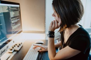 Eine Frau arbeitet an ihrem Rechner und nutzt dabei Programmiersprache. Low-Code-Entwicklung soll ihre Arbeit leichter machen. Bild: Unsplash/Kelly Sikkema