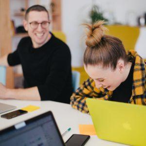 Eine Frau und eine Mann lachen herzlich während der Arbeit. Das Ergebnis von Feel-Good-Management? Bild: Unsplash/Leon