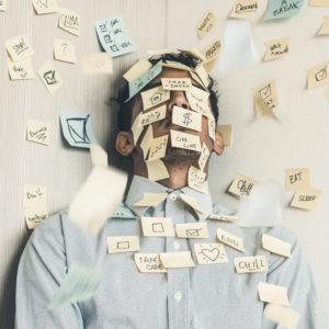 Ein Mann ist übersät mit Sticky Notes und erstickt in seinen Aufgaben. Ein Fall von Fake Work? Bild: Unsplash/Luis Villasmil