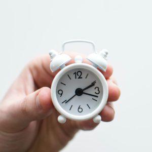 Eine Hand hält einen sehr kleinen Wecker vor die Kamera-Linse. Es geht um Zeitverschwendung durch Fake Work. Bild: Unsplash/Lukas Blazek