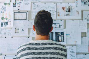 Ein Mann steht vor einem Whiteboard mit vielen Informationen. Könnte seine Forschung für Cyberspionage interessant sein?