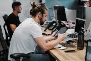 Zu sehen ist ein Büroszene; im Vordergrund arbeitet ein Mann an Tablet, PC und Handy; vielleicht hat er über die Low-Code-Entwicklung eine Anwendung erstellt und prüft sie auf verschiedenen Endgeräten. Bild: Unsplash/Studio Republic