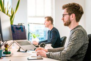 Zu sehen sind zwei Männer an Ihren Arbeitsplätzen. Sie arbeiten in der IT-Abteilung und verwalten die hyperkonvergente Infrastruktur. Bild: Unsplash/Tim van der Kuip